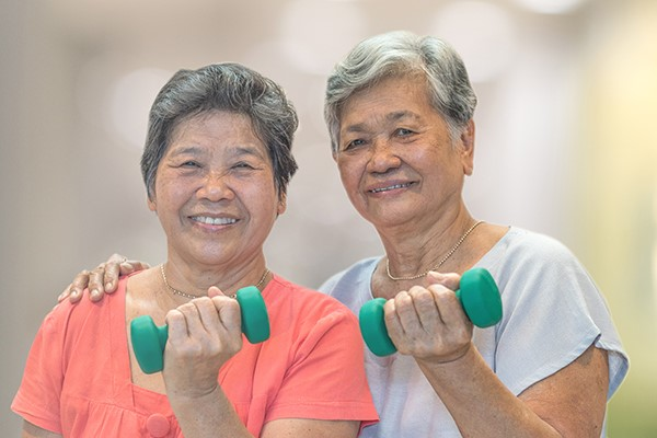 two older women using weights to exercise and smiling