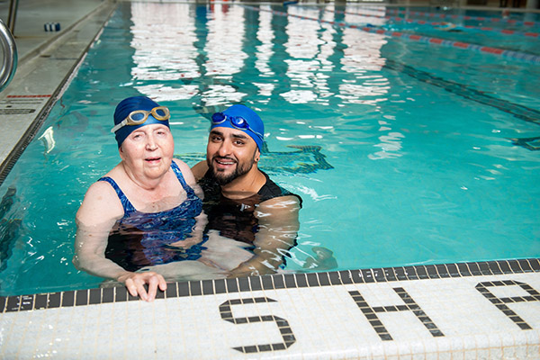 YMCA member Lea in the pool with YMCA staff member Naryan.