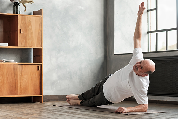 man doing a side plank exercise at living room.
