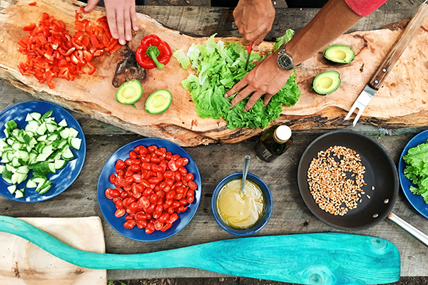 A variety of plates with vegetables, grains and oils. Two different people's hands seen cutting some lettuce and avocados and peppers.