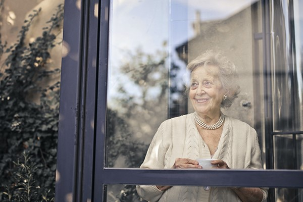 Woman looking out the window and drinking a coffee
