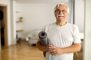 Happy senior man holding bottle of water and exercise mat in the living room and looking at camera.