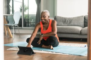 woman sitting on a yoga mat looking at a tablet and smiling